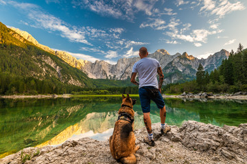 Adventure Man Standing With Dog at Beautiful Lake, Fusine Lake , Italy