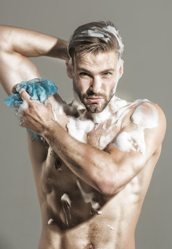 Spa, hygiene, relax. Naked man taking shower with foam. Man in shower. Fitness man with muscular body taking shower in morning. Handsome muscular man in shower. Sexy guy wash with sponge in bathroom.