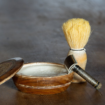 wooden bowl of shaving soap with razor and shaving brush on wooden table surface with copy space