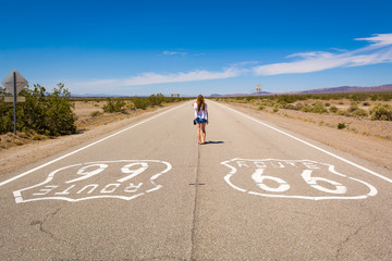 Poster Route 66 Young woman standing on the Route 66 road in Californian desert. United States