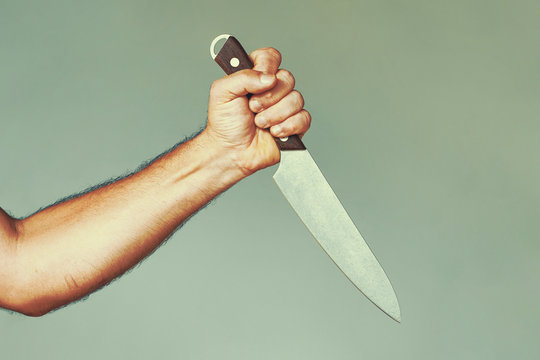 Hand of caucasian man holding a knife isolated on a gray background. Man hold knife - aggression. Big kitchen knife in man hand. Large kitchen knife in a man's hand.