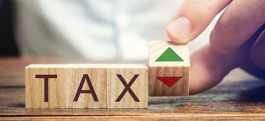Wooden blocks with the word Tax and up and down arrows. Business and finance concept. Taxes and taxation. The tax burden
