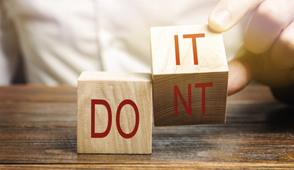 Businessman puts wooden blocks with the words Do it and don't. The concept of motivation and self-development. Goal achievement.