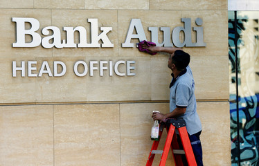 A worker cleans the logo of Bank Audi in Beirut