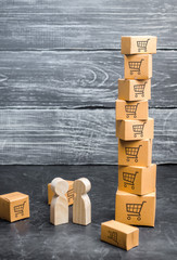 Two wooden people stand near a tower of boxes. buyer and seller, manufacturer and retailer. Business and commerce. Discussion of the terms of the trading deal, the purchase of goods and services.