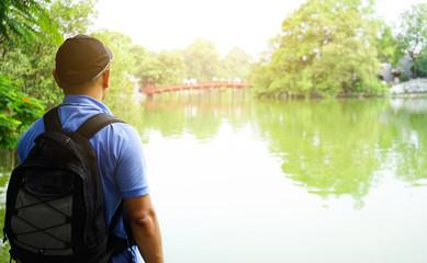 Male tourists Stand by the lake, look at the bridge Red Bridge in Hoan Kiem Lake, Hanoi, Vietnam Wall mural