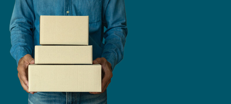 Online shopping, a young start up small business owner raises a cardboard box at work. Small Business Entrepreneurs SME, Work With Box At Home, Online Sales, E-Commerce, Packaging.with clipping path