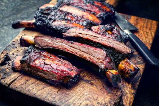 Barbecue burnt chuck beef ribs marinated with hot chili sauce sliced as closeup on an old rustic wooden cutting board - vintage