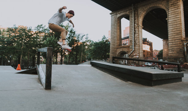 Young boy performing tricks with the skateboard in a skate park