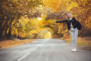 young woman stands and waits on an asphalt road in cold autumn weather, a girl tries to get from a suburban highway by a hitchhiker showing a hand gesture Fototapete