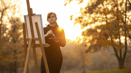 silhouette of young woman artist painting a picture on the easel, girl figure with a brush and a palette of colors on the background of autumn landscape, a concept of hobby and art