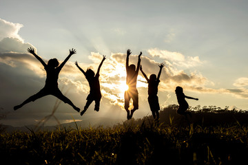 Silhouette group of happy children jumping playing on mountain at sunset, summer time Wall mural
