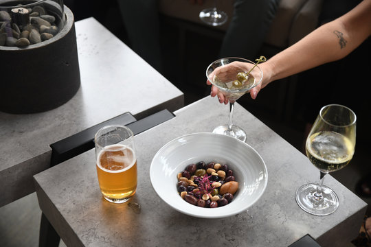 Woman's hand picking up drink at table