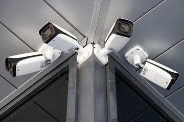 Bottom view close-up of four white surveillance cameras