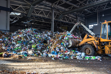 excavator stacks trash in big pile at sorting modern waste recycling processing plant. Separate and sorting garbage collection. Recycling and storage of waste