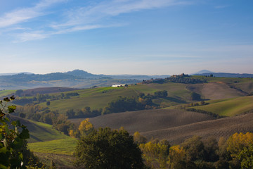 landscape rolling green hills of Italy in October blue bright sky