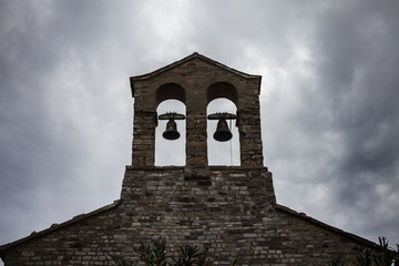 Old stone church steeple of bells overcast moody sky