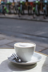 Cup of coffee on table at outdoor cafe in Paris France street and bicycle rack in the background