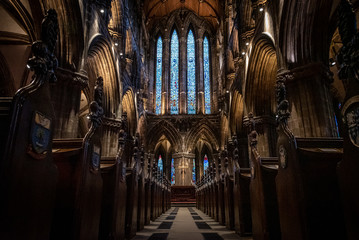 GLASGOW, SCOTLAND, DECEMBER 16, 2018: Magnificent perspective view of interiors of Glasgow Cathedral, known as High Kirk or St. Mungo, with huge stained glasses. Scottish Gothic architecture.