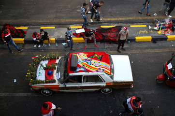 An Iraqi demonstrator rides a decorated car during ongoing anti-government protests, in Baghdad