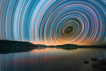 Beautiful night landscape with small lake and mountains. The colorful star trails on the sky. Night time lapse photography.. Fotomurales