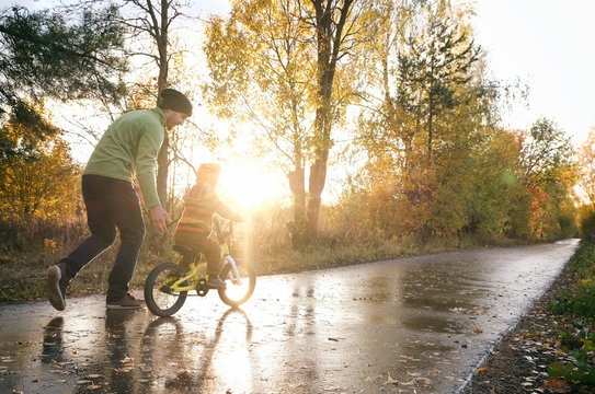 Father teaches his little child to ride bike in autumn park. Happy family moments. Time together dad and son. Candid lifestyle image.
