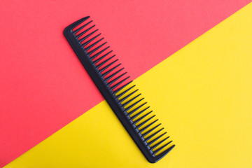 Black hair comb in the center of the bicolor background. Top view. Copy space.
