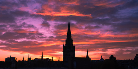 Silhouette of cityscape of Aberdeen in Scotland. Church tower and buildings in the city center. Beautiful  colorful sunset in Aberdeen. Pink and blue sky. Low light photography.