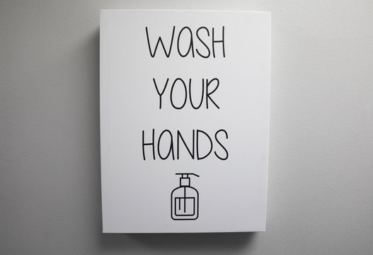 sign says to wash your hands