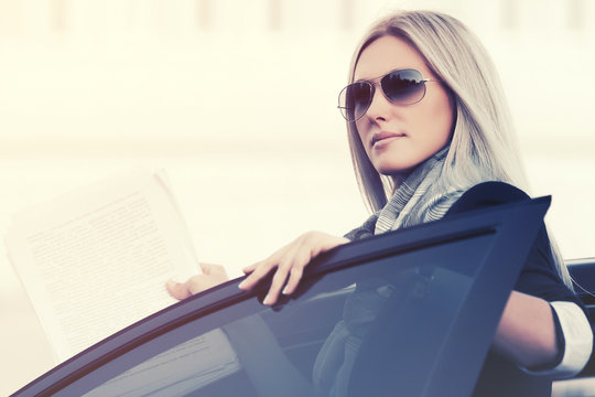Young fashion blonde business woman in sunglasses outside her car
