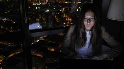 Brunette woman in glasses is working on her computer near the window in home at night. Young...