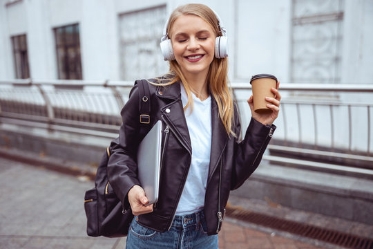 Modern young girl with eyes closed enjoying music
