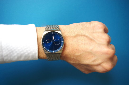 Business man pointing at hand watch, success and business concept, time management