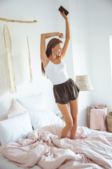 Happy long haired girl dancing on her bed