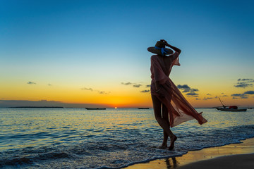 Beautiful girl in a straw hat and pareo on the beach during sunset of Zanzibar island, Tanzania, east Africa