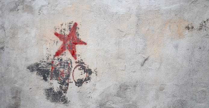 Communistic symbol: Grungy red star graffiti on and old wall