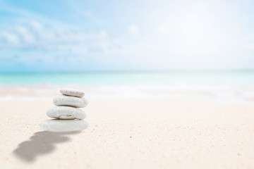 Wall Murals Stones in Sand Zen stones on the beach for relaxing meditation. Pyramid stones with sun and blurred background