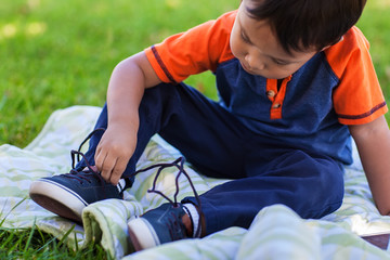 A cute boy learning to tie his shoe laces while relaxing in a green lawn.