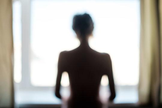 Unknown female person standing near window alone.