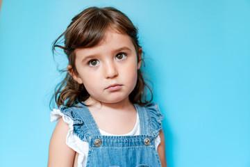 Portrait of sad girl, blue background