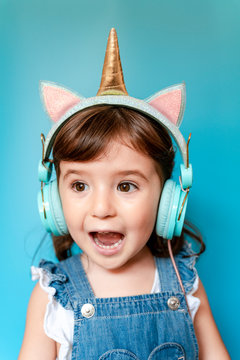 Portrait of cute little girl listening music and singing with unicorn shaped earphones on blue background