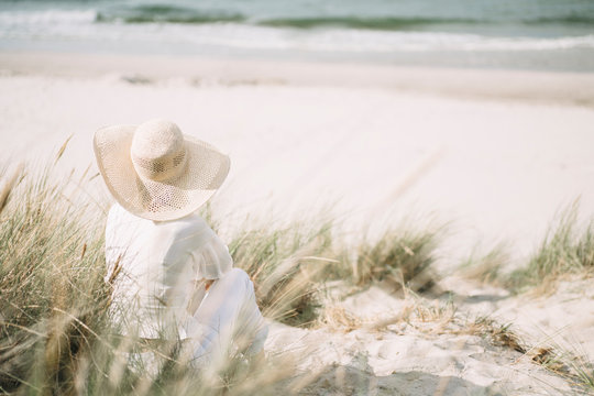 Back view of woman wearing summer hat sitting on the beach looking at the sea, Ruegen, Germany