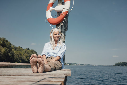 Senior woman sitting on jetty, listening music by the sea