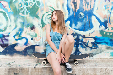 Young woman sitting on skateboard in front of graffiti