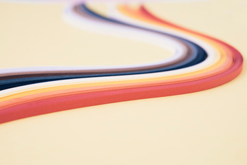 Close-up of quilling papers with swirl pattern on beige background