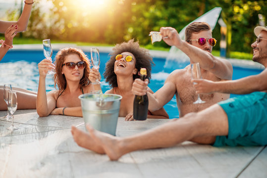 Group of friends having party in swimming pool