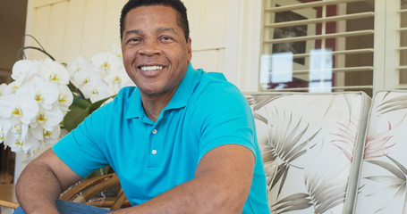 Portrait of attractive Black man smiling and sitting on porch looking at camera
