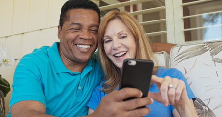 Close up of happy older couple sitting on porch and using smartphone together