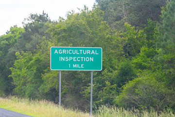 Mobile, Alabama city highway interstate 10 and closeup of sign for agricultural inspection station in one mile exit Wall mural