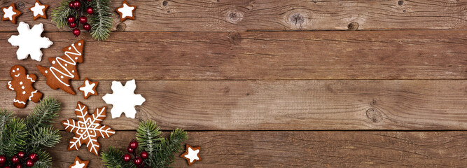 Wall Mural - Christmas gingerbread cookies and tree branches. Above view corner border banner on a rustic wood background.